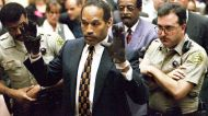 O.J. Simpson tries on the blood-stained gloves alleged to have been used in the killing of Nicole Simpson and Ron Goldman.