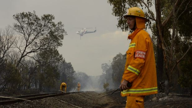 CFA firefighter put out railway sleepers along the Stony Point railway line, near Somerville, on Tuesday..