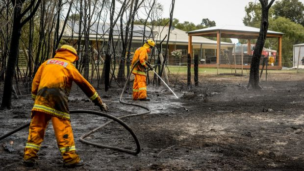 Firefighters put out spot fires at the back of a Gomms Road home at Somerville on Tuesday.