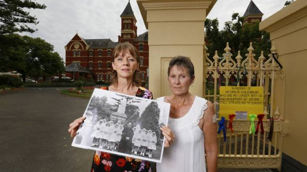 Gabby Short and Wendy Eldridge with a photo of the orphanage girls with paedophile priest Gerald Ridsdale.