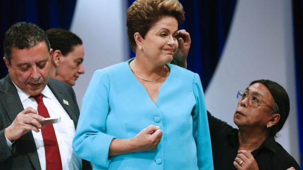 Brazilian President Dilma Rousseff gets a touch-up by a make-up artist, while her trusted aide, Joao Santana, left, ...