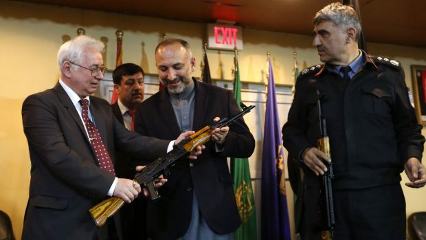 Russian Federation Ambassador Alexander Mantytskiy, left, hands over an AK-47 to Afghan National Security Advisor ...