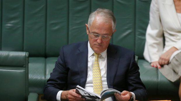 Prime Minister Malcolm Turnbull with the defence white paper during question time on Thursday.