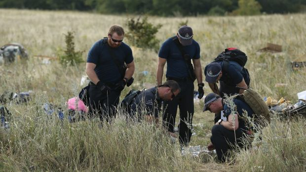 Australian Federal Police officers and their Dutch coutnerparts collect human remains from the MH17 crash site in the ...