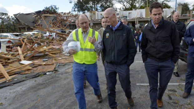 Florida Governor Rick Scott, centre, tours an apartment complex that was destroyed by a tornado in Pensacola, Florida on ...