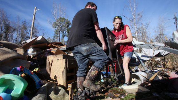 Clint Lowery, left, and Amanda Lowery, right, remove a deep fryer from the family's tornado damaged mobile home in ...