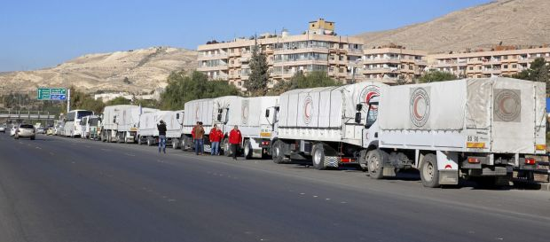 A convoy of humanitarian aid waits in Damascus before making its way into the government besieged rebel-held towns of ...