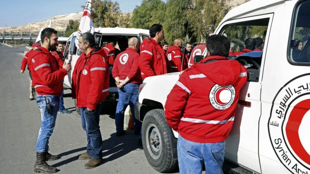 Syrian Arab Red Crescent staff get ready to accompany an aid convoy into rebel-held towns in the Damascus countryside.