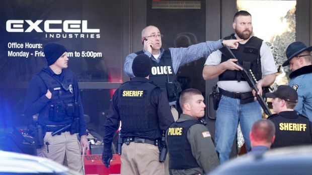 Police guard the front door of Excel Industries in Hesston after the shooting.