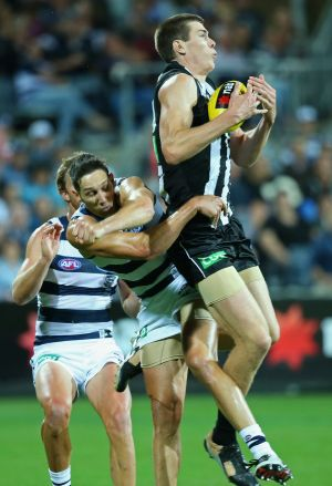 Mason Cox of the Magpies marks in front of Harry Taylor of the Cats.