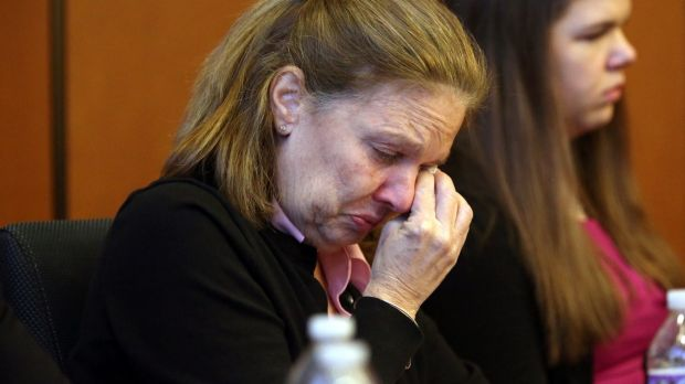 Peggie Ritzer listens to her husband, Thomas, read his witness impact statement.
