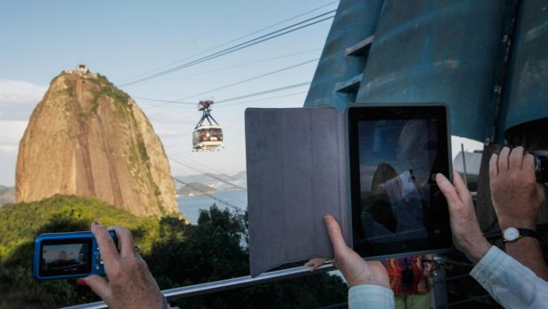 Visitors gather and take photos of the famed Sugar Loaf Mountain, a landmark tourist destination in Rio. The Zika virus ...