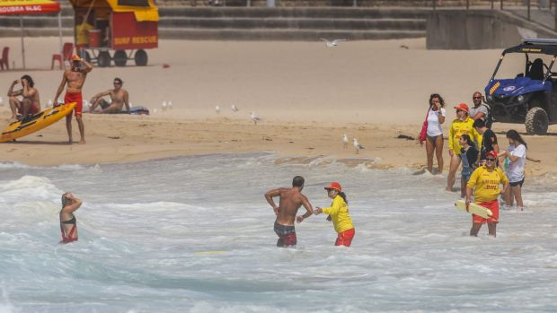A surfer is helped ashore after losing his board at Maroubra.