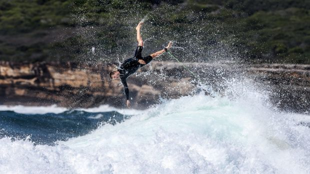A surfer flies off the back of a large wave at Maroubra.