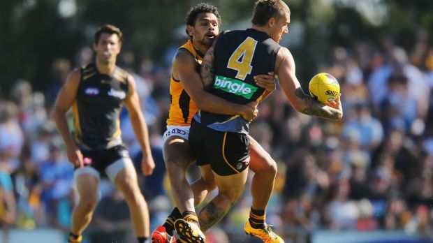 You're going nowhere... Hawthorn's Cyril Rioli gets a firm grip on Dustin Martin of the Tigers during the NAB Challenge ...