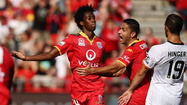 Bruce Kamau of Adelaide United celebrates with teammates after he scored.