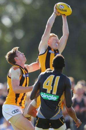 James Sicily of the Hawks grabs a mark as teammate Ryan Schoenmakers and Mabior Chol of the Tigers  watch.