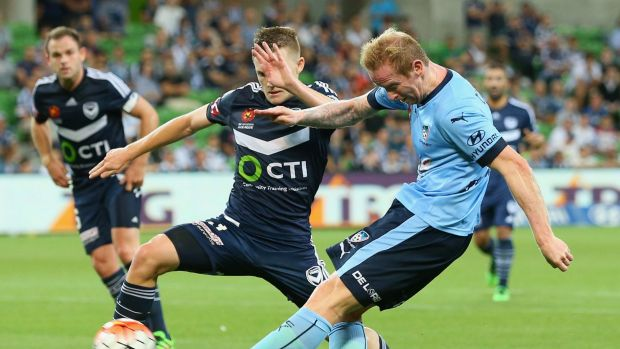 David Carney of Sydney FC kicks past Scott Galloway of the Victory.