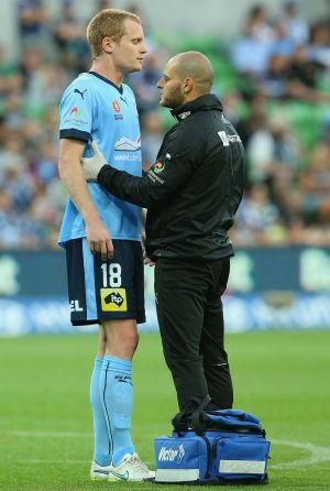 Matt Simon of Sydney FC is attended to by a trainer after he was substituted during the game against Melbourne Victory.