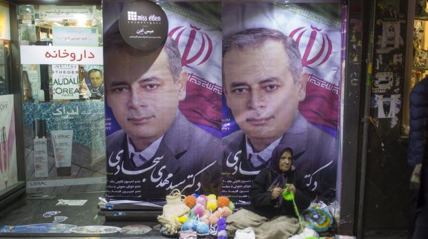 People walk past electoral posters in Tehran, Iran on Friday.