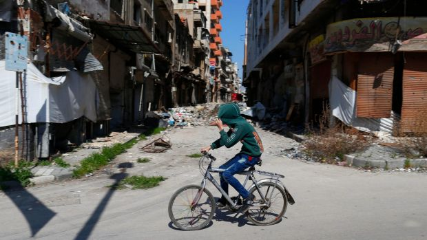 A Syrian boy covers his face as he rides a bicycle through a devastated part of the old city of Homs.