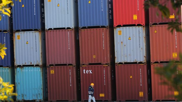A port worker walks past a pile of cargo at a container terminal in Tokyo. Japan is experiencing sluggish exports.