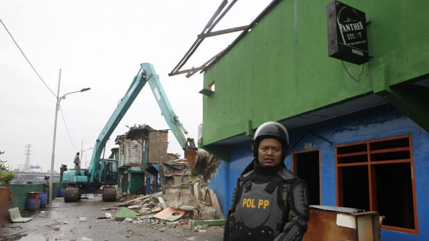 Officers with heavy equipment destroy buildings in Kalijodo after residents and sex workers were evicted.