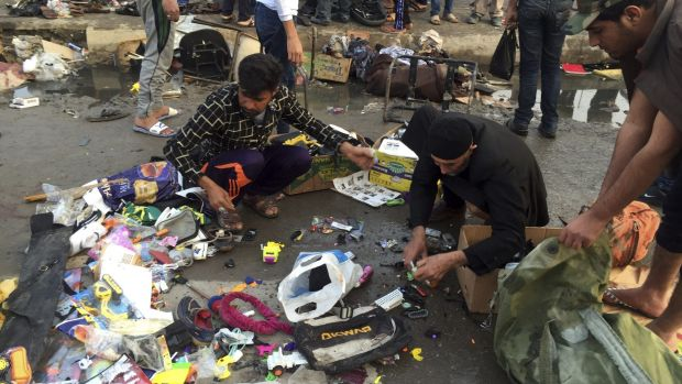 Street vendors collect their belongings after a deadly bombing attack in Sadr City, Baghdad, on Sunday.