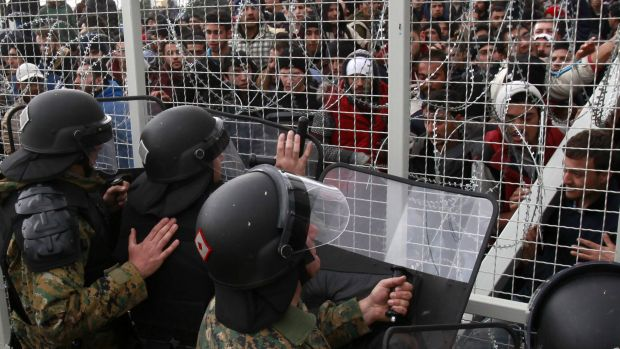 Stranded refugees and migrants try to break an iron fence from the Greek side of the border as Macedonian policemen push ...
