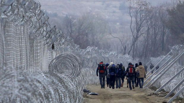 Refugees and migrants, who entered Macedonia from Greece illegally, walk between the two lines of the protective fence ...