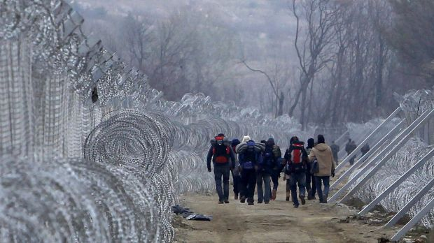 Refugees and migrants who entered Macedonia from Greece illegally walk between the two lines of the protective border ...