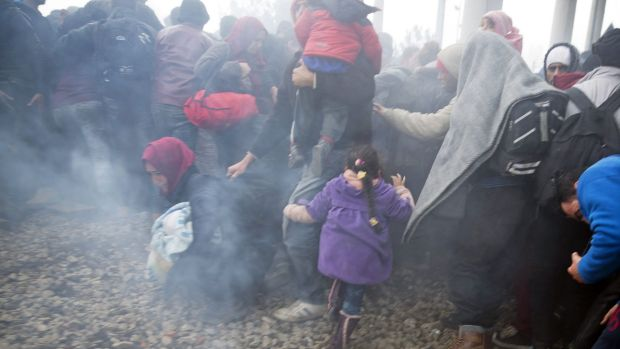 People run away after Macedonian police fired tear gas at a group of people who tried to push their way into Macedonia, ...