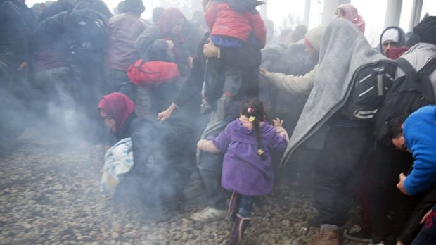 People run away after Macedonian police fired tear gas at a group trying to push their way into Macedonia near the ...