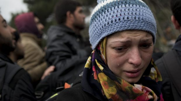A woman cries as refugees and migrants protest in front of the border gate that separates Greece with Macedonia near the ...