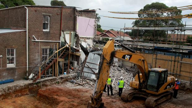 An excavator demolishes the building, which was structurally unsafe.