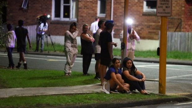 Papatoetoe residents look on as police investigate the scene of where a woman was thrown from her car.