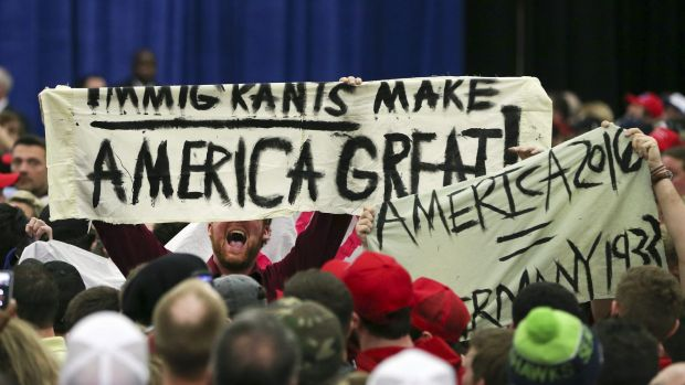 A protester holds up a sign as he disrupts a rally for Republican presidential candidate Donald Trump.