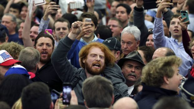 A protester is escorted out of a rally for Republican presidential candidate Donald Trump in Louisville, Kentucky.