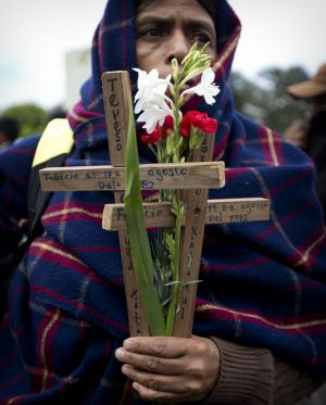 An indigenous woman holds wooden crosses and flowers on the National Day of Dignity for the Victims of Armed Internal ...
