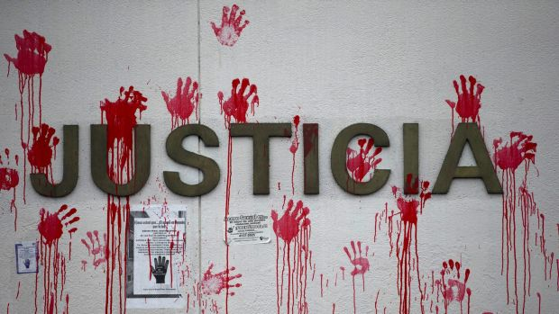 """Red handprints cover the word """"Justice"""" on the outside wall of the Supreme Court building during a protest by human ..."""