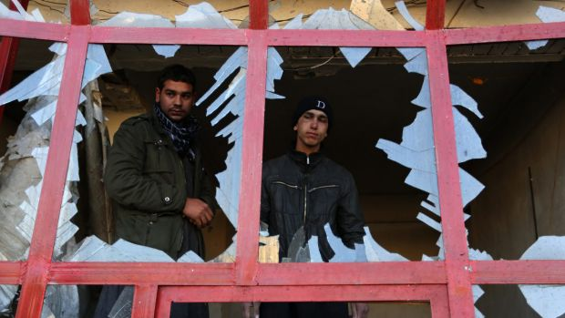 Normal business will resume ... a shopkeeper looks out from his workplace after a suicide bomb in Kabul.