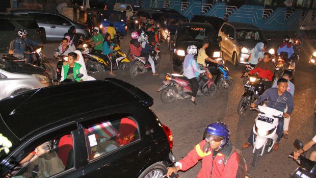 People try to reach higher ground in Padang, West Sumatra, after a strong earthquake.
