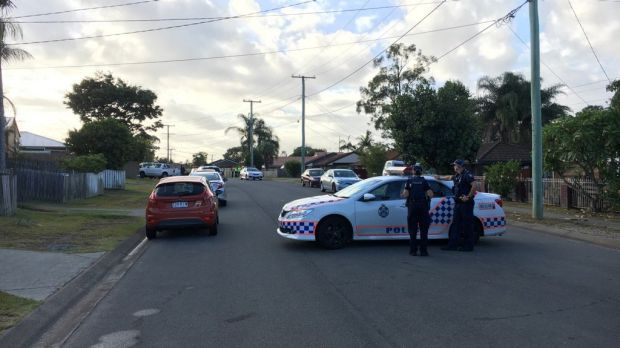 Police have blocked off Barossa Street, Kingston, as they negotiate with an armed man holding a small child hostage.