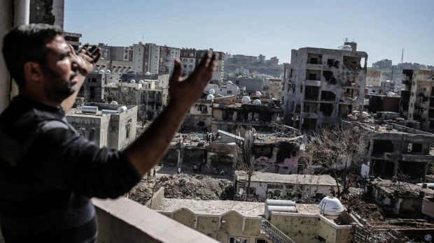 A man gestures as he looks at the ruined houses after returning to Cizre.