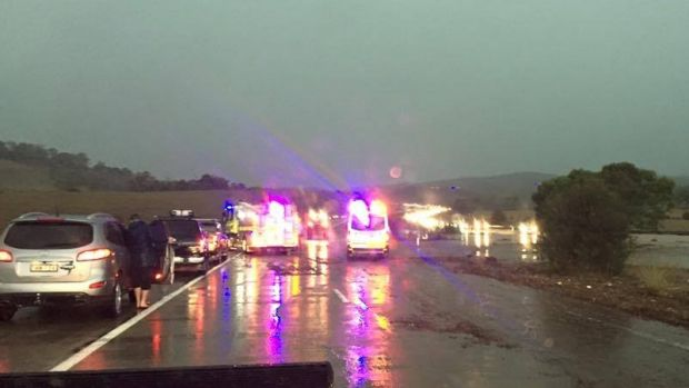 Emergency crews respond to cars swept off the Federal Highway due to flooding.