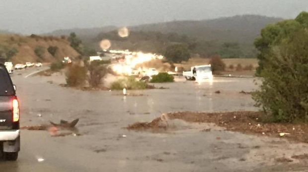 Vehicles continue to drive through flood waters on Federal Highway. A partially submerged car is in the centre of the ...