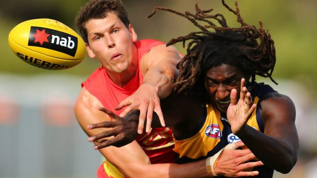 Daniel Currie of the Suns and Nic Naitanui of the Eagles contest the ruck.