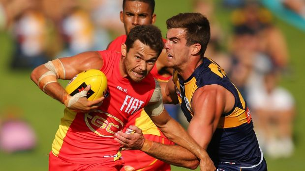 Jarrod Harbrow of the Suns looks to break to break a atackle by Scott Lycett of the Eagles.