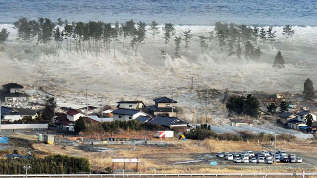 Waves from the tsunami hit residences after a powerful earthquake in Natori, Miyagi prefecture, in March 2011.