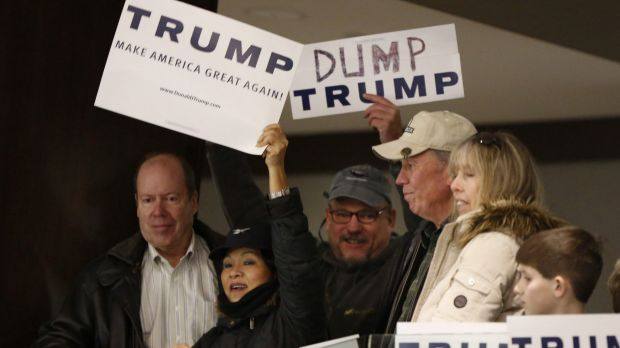 """A Donald Trump supporter holds up a sign trying to block Walter Skold, who is holding a """"Dump Trump"""" sign at a campaign ..."""